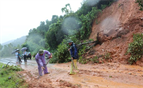 Workers clear a road affected by landslides to avoid traffic congestion